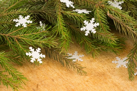 The branches of Christmas trees on the background of wooden boards and snowflakes. Christmas and New Years background. Stock Photo