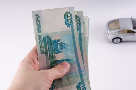 A hand holding a pile of thousand-dollar ruble notes. Russian currency on a white background.