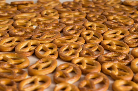 bakery products: Background texture of salted savory mini pretzels in the traditional looped knot shape. Top view full frame from overhead.