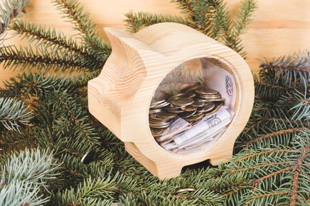 Yellow wooden piggy bank with russian ruble coins and banknotes. Christmas and New Year's wooden background with branches of spruce