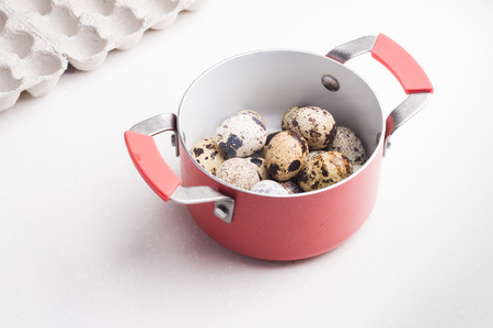 Quail eggs in a red saucepan, cardboard packaging on white stone background. Vegetarian food. Eco products  concept.