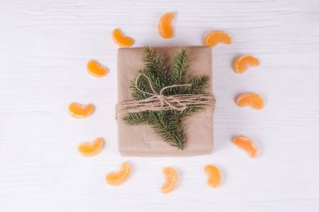 Christmas gift box on a white wooden background. Frame of fir branches, tangerine slices. Christmas & New Year composition. Stock Photo
