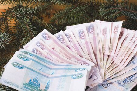 russian ruble banknotes at Christmas or New Year's wooden background with branches of spruce