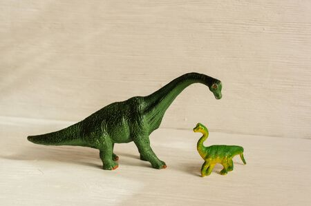figurine of a bracheosaurus and its cub. offspring care concept. plastic dinosaur figures of extinct ancient creatures and  favorite toys of kids Stock Photo