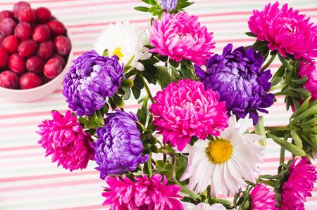 red plums in bowl and bouquet of chrysanthemums on  colorful striped tablecloth. Organic red plums. 写真素材 - 132049650