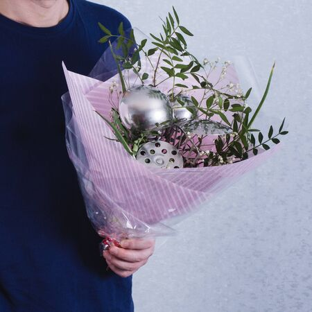 A man gives a bouquet of flowers and ladles. concept of patriarchal society and gender inequality. Sexism and feminism.