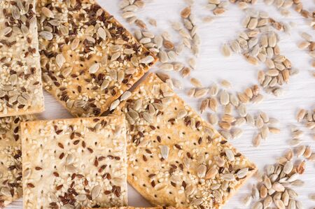 Stack of crispy wheat cakes with sesame, flax and sunflower seeds on white wooden background. Top view. vegetarian food, eco food concepts