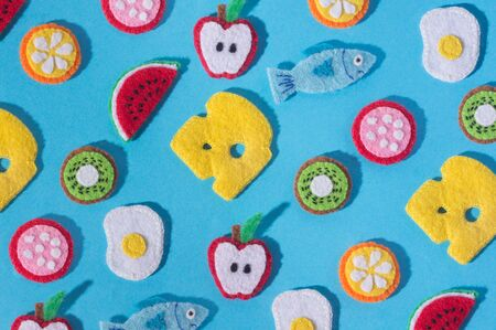 Toys in the form of food and fruits hand made of felt on blue background. Hand sewing Фото со стока