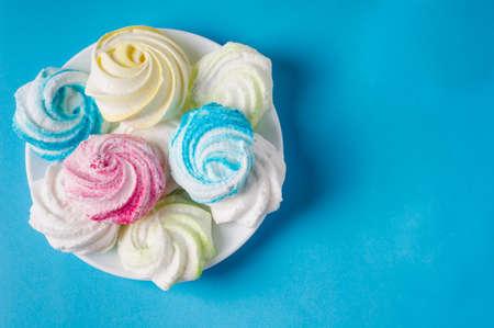 Homemade sweet colored meringue on white background. Dessert.