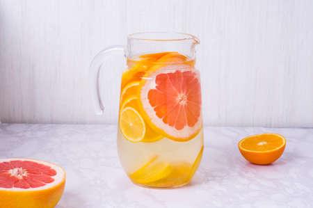 Lemonade pitcher with oranges, lemons and grapefruit on table. glasses of lemonade shot on white table