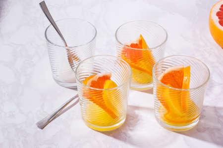 Lemonade with oranges, lemons and grapefruit on table. glasses of lemonade shot on white table