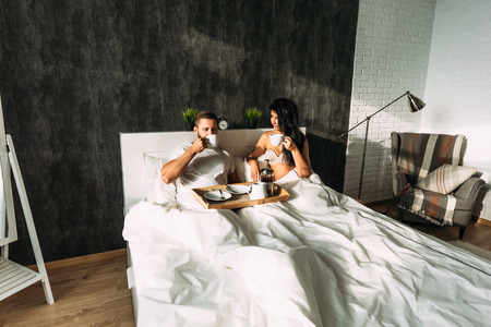 Loving couple having breakfast in bed. Guy and girl in bed. Breakfast in bed. Tea in bed. The relationship between man and woman. Loving couple Morning lovers. Family relationships. Good morning 版權商用圖片