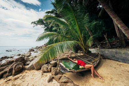 Beautiful girl on a paradise beach. Girl sunbathing on the beach. Beautiful woman on the beach. A girl on a beautiful island. The girl on the Islands. Sea. Beach. Sand. Boat. Model in swimsuit. 免版税图像