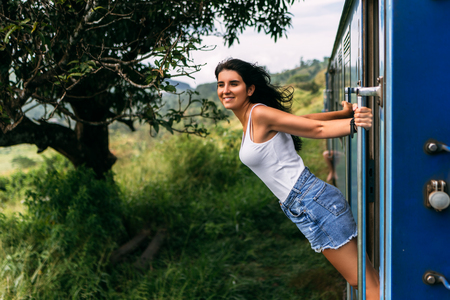 The girl travels by train to beautiful places. Beautiful girl traveling by train among mountains. Travel by train. Traveling to Asia. Trains Sri Lanka. Railway transport. Railway. Transport Asia
