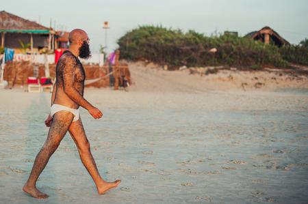 Paseos blancos desconocidos en la playa india durante la puesta de sol. Cuerpo peludo. Un hombre con barba