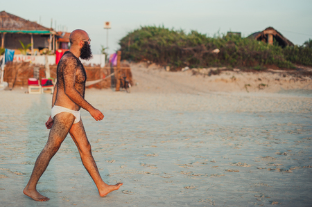Unknown white walks on Indian beach during sunset. Hairy body. A man with a beard