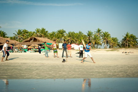 Friends play cricket on the beach of GOA in India. The guys play Indian baseball on the beach. Indian national sport. The game of cricket at sunset Editorial