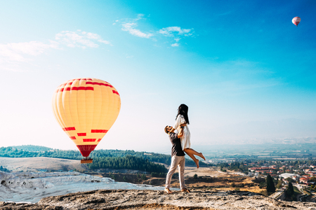 Couple in love among balloons. A guy proposes to a girl. Couple in love in Pamukkale. Couple in Turkey. Honeymoon in the mountains. Man and woman traveling. Flying on balloons. Wedding. Journey. Love