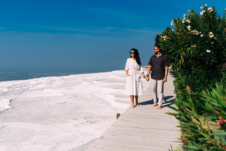 Man and woman traveling. Couple in love walking. Couple in Pamukkale. Travelling to Turkey. Lover. Honeymoon trip. Guy and girl are traveling. Wedding travel. Newly married couple. Honeymoon