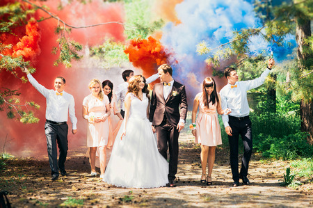Wedding guests. Bride and groom kissing at wedding ceremony. Funny guests at the wedding. Bride, groom and guests outdoors. Wedding day. Photo session