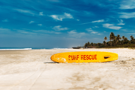 Bright yellow surfing on the sandy beach in the afternoon. Life saving yellow board with surf rescue sign. Rescue surf board. Board for rescue of the drowning.