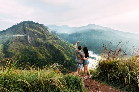 Man and woman holding hands taking selfie on the peak of mountain. Archivio Fotografico