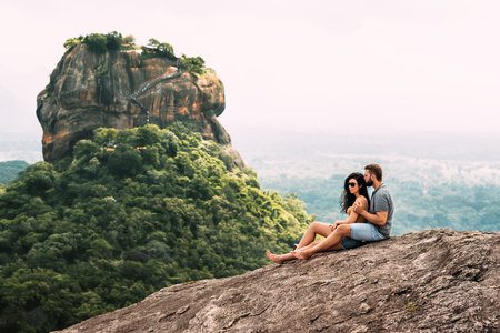 A couple in love on a rock admires the beautiful views in Sigiriya.