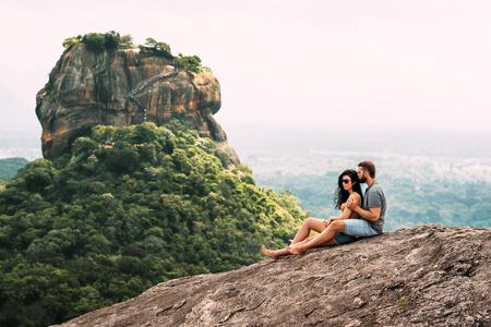 Una pareja enamorada en una roca admira las hermosas vistas de Sigiriya.