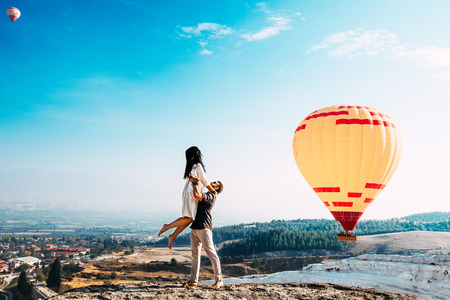 Man lifted up a woman on his hands. Couple in love among balloons in Pamukkale. Imagens