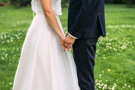 Hands of bride and groom. New young couple holding hands after their wedding. Young married couple holding hands, ceremony wedding day. Closeup view of married couple holding hands