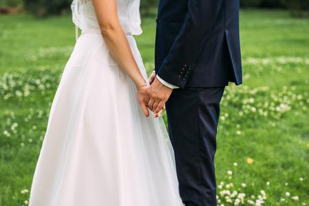 Ręce panny młodej i pana młodego. Nowa młoda para trzymając się za ręce po ślubie. Młode małżeństwo trzymając się za ręce, uroczystość ślubu. Widok zbliżenie małżeństwa trzymającego się za ręce
