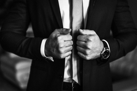 Man in business suit. A man puts on a suit. Close-up business stylish man buttoning his jacket. A businessman in an expensive suit.  Black and white photo 版權商用圖片