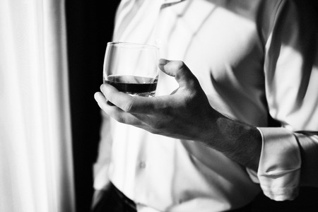 Young man with glass on whiskey near window. Man drinking whiskey at the window. Drink whiskey, cognac, close-up. Hand with a glass of alcohol. Black and white photo