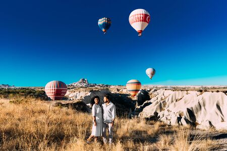 Turkey, Cappadocia - October 10, 2018: Couple in love among balloons. Happy couple in Cappadocia. Honeymoon in the mountains. Man and woman traveling. Flying on balloons. Festival of balloons 新聞圖片