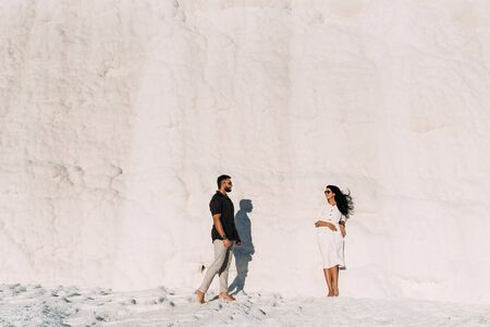 The couple travels to the picturesque places of Turkey. Man and woman at sunset. Stylish couple in love. A couple in love travels to Turkey, Pamukkale. Man and woman standing against the wall