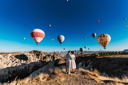 Couple travels the world. Happy and loving couple among balloons in Turkey. Married couple on vacation. Tourists in Cappadocia. Man and woman resting in Turkey. Flying balloons at sunrise. Honeymoon