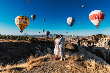 Couple travels the world. Honeymoon trip. Married couple on vacation. Tourists in Cappadocia. Man and woman resting in Turkey. Flying balloons at sunrise. World tour. Man and woman among balloons