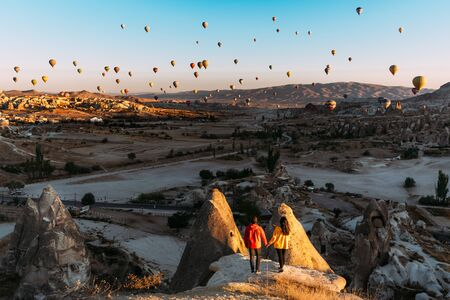 Man and woman greet the dawn among balloons. Couple in love among balloons.  Travelers in the mountains of Cappadocia, Turkey. Man and woman traveling. Flying on balloons. Festival of balloons