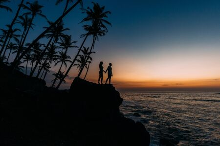 Silhouette of loving couple on sea. Man and woman at sunset. Honeymoon on the Islands. Man and woman meet sunset. Happy loving couple. Silhouette lovers. Wedding travel. Loving couple. Honeymoon trip 版權商用圖片