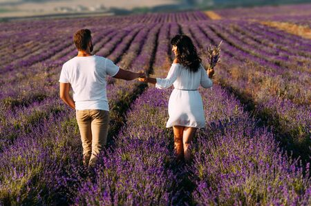 Happy couple on lavender fields. Man and woman in the flower fields. Honeymoon trip. Couple travels the world. Lavender meadows. Wedding travel. Follow me. Man and woman holding hands view from back