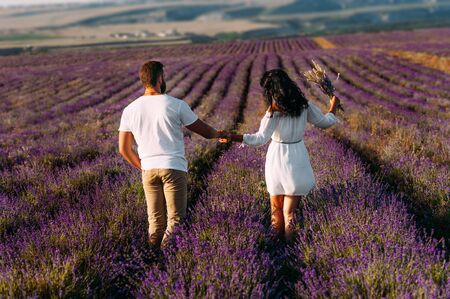 Loving couple holding hands on lavender fields. Happy couple on flower fields rear view. Man and woman traveling. Couple at sunset. Honeymoon trip. Beautiful couple at sunset among the flowers 版權商用圖片