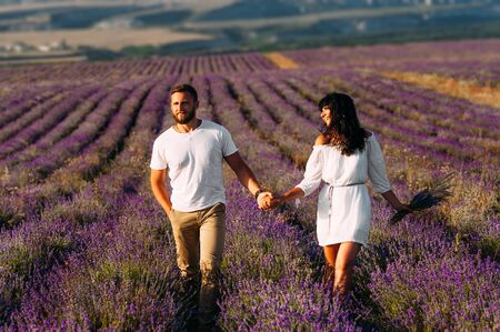 Happy couple holding hands in lavender fields. Couple in love on flower fields. Honeymoon trip. Follow me. Beautiful couple at sunset among the flower field. Couple walking among the flowers