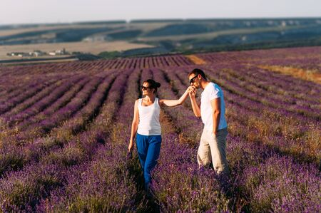 A man makes a proposal to a girl on a flower field. Happy couple in the lavender fields. Honeymoon trip. A man kisses a womans hand at sunset. A couple in love walks among the flowers