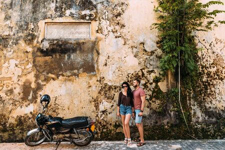 The couple travels on a scooter in Sri Lanka. Man and woman traveling. The couple travels to Asia. Independent travel on motorcycle. Man and woman at the old wall 版權商用圖片