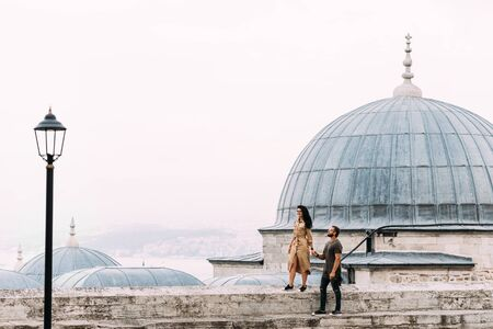 Couple walking on the roofs of Istanbul. Happy couple traveling to Turkey. Man and woman walking around Istanbul. Tourists in Turkey. Couple in Eastern country. Traveling couple near the mosque