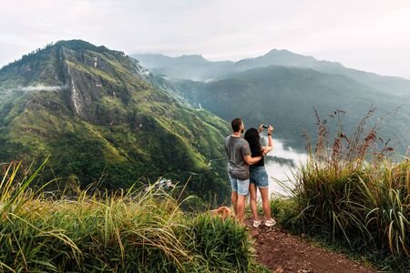 A couple in love travels to Sri Lanka. The couple travels the world. A man and a woman greet dawn in the Ella mountains, Sri Lanka. Travel to Asia.  The couple admires the beautiful scenery.
