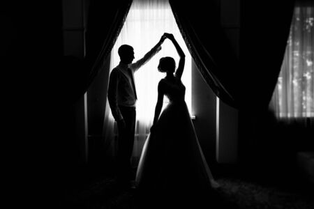 Bride and groom at the window. Silhouette of the bride and groom at the window. Silhouette of newlyweds. Newlyweds at the window. Dance of the newlyweds. The bride and groom waltz. Wedding dance 版權商用圖片