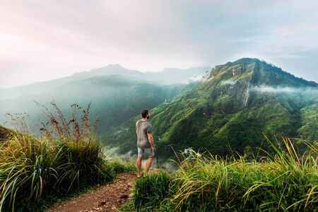 A man stands with his back in the mountains. A man travels in Asia. Travel to Sri Lanka. Traveler in the mountains. A man enjoys a beautiful view of the mountains. Man at sunrise in the mountains