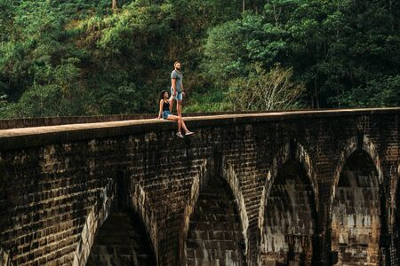 Couple in love on vacation. Man and woman traveling around Asia. The couple travels to Sri Lanka. Happy couple travels the world. Travellers in Asia. Follow me. Tourists on the nine-arch bridge