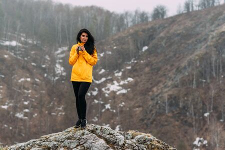 Traveler holding a mug of hot tea in the mountains. Woman in sportswear in the mountains. Climb to the top of the mountain. Girl in a yellow jacket in cloudy weather. Woman on top of a mountain